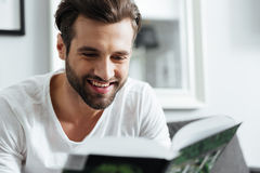 Smiling man reading book. Looking aside. Royalty Free Stock Photos