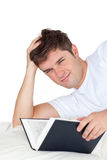 Smiling man reading a book lying on his bed Royalty Free Stock Photography