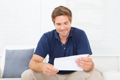 Smiling Man Reading Letter At Home Royalty Free Stock Image