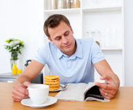 Smiling man reading a newspaper Royalty Free Stock Image