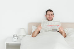 Smiling man reading a newspaper Royalty Free Stock Photo