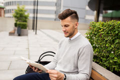 Smiling man reading newspaper on city street bench Royalty Free Stock Photography
