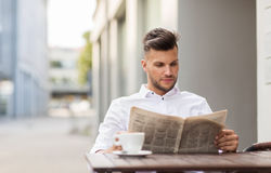 Smiling man reading newspaper at city street cafe Stock Photography