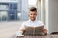 Smiling man reading newspaper at city street cafe. Business, mass media and people concept - smiling man reading newspaper with coffee at city street cafe stock image