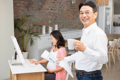 Smiling man reading newspaper and having coffee Stock Photos