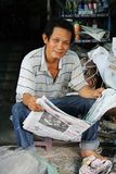 Man reading newspaper, Ho Chi Minh City, Vietnam. A smiling man reading a newspaper in Ho Chi Minh City, Vietnam Stock Photos