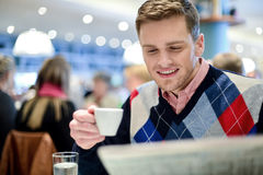 Smiling man reading newspaper at restaurant Stock Images
