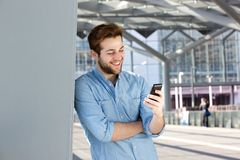 Smiling man reading text message on mobile phone Royalty Free Stock Image