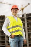Smiling young man in red hardhat and green safety vest standing on building site. Smiling man in red hardhat and green safety vest standing on building site Stock Photos