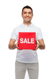 Smiling man with red sale sigh Royalty Free Stock Image