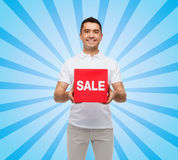 Smiling man with red sale sigh Stock Photos