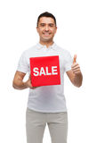 Smiling man with red sale sigh showing thumbs up Royalty Free Stock Photos