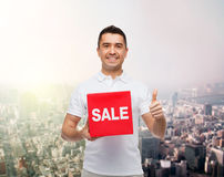 Smiling man with red sale sigh showing thumbs up Stock Photos