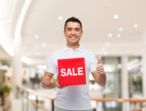 Smiling man with red sale sigh showing thumbs up Stock Image
