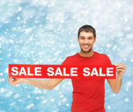 Smiling man in red shirt with sale sign Stock Images