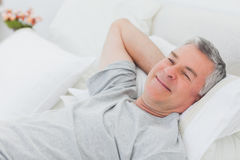 Smiling man relaxing in bed Royalty Free Stock Image
