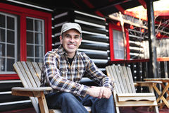 Smiling man relaxing at cottage. Smiling man sitting on cottage deck in wooden adirondack chair stock photo