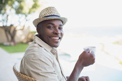 Smiling man relaxing in his garden having coffee Royalty Free Stock Photography