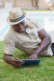 Smiling man relaxing in his garden using tablet pc Stock Photo