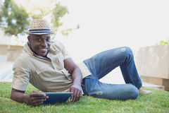 Smiling man relaxing in his garden using tablet pc Royalty Free Stock Image