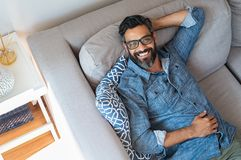 Smiling man relaxing at home royalty free stock images