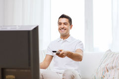 Smiling man with remote control watching tv Royalty Free Stock Images