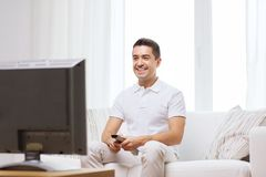 Smiling man with remote control watching tv Stock Photo