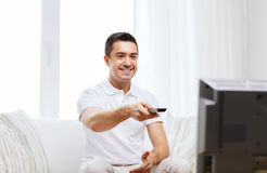 Smiling man with remote control watching tv Royalty Free Stock Photo