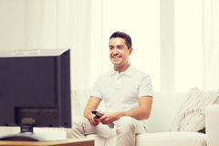 Smiling man with remote control watching tv Royalty Free Stock Photos