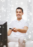 Smiling man with remote control watching tv Royalty Free Stock Photography