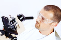 Smiling man researching on a microscope Stock Images