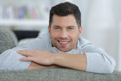 Smiling man resting on sofa at home Royalty Free Stock Photo