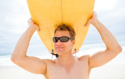 Smiling man resting surfboard on head at beach. Smiling male surfer resting surfboard on head at beach with ocean and sky in background Stock Photography