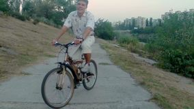 Smiling man riding bicycle, city park near river, aerial shot. Stock footage stock video footage