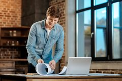 Smiling man rolling a blueprint in the study. Finishing work. Pleasant cheerful man standing in the study and rolling a blueprint, having finished his work royalty free stock photo
