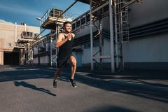 Smiling man running fast in industrial city background. Sport, athletics, fitness, jogging activity royalty free stock photos