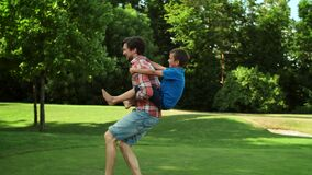 Man running in field with boy on back. Father giving son piggyback riding