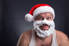 Smiling man in Santa Claus hat. Happy smiling man in Santa Claus hat with shaving foam on his face Stock Photo
