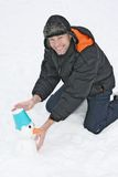 Smiling man sculpts snowman Stock Photo