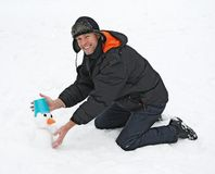 Smiling man sculpts snowman Royalty Free Stock Photos