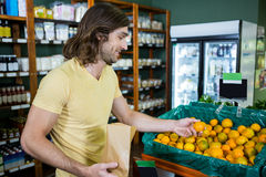Smiling man selecting oranges in organic section Stock Images