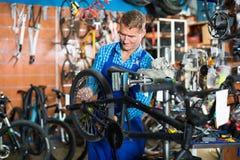 Smiling man seller wearing uniform fixing bike. In sport store Stock Photo