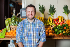 Smiling man selling grapes in shop. Portrait of smiling man in shirt selling vegetables in a shop. Boxes with fruits and vegetables on the background royalty free stock images