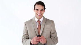 Smiling man sending a text with his cellphone stock footage