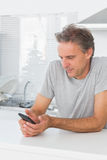 Smiling man sending text message in kitchen. At home sitting at counter Stock Photo