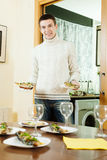 Smiling man serving cooked fish Royalty Free Stock Photography