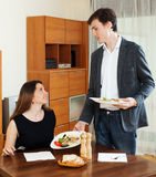 Smiling man serving dinner to beloved woman Stock Photo