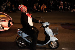 Smiling man in Seuss hat rides motor scooter in Oregon holiday parade. Corvallis, OR, Nov 28, 2015: smiling man in Seuss hat rides motor scooter in holiday Royalty Free Stock Photos