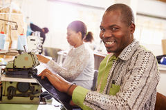Smiling man sewing at a community workshop, South Africa Stock Images