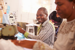 Smiling man sewing at a community workshop, South Africa Royalty Free Stock Photos